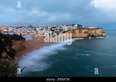 View of Carvoeiro village surrounded by sandy beach and clear sea at dusk Lagoa Municipality Algarve Portugal Europe - Stock Photo
