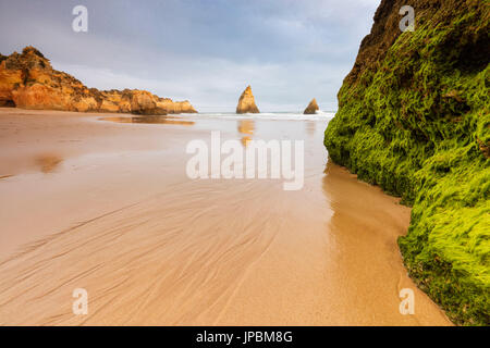 Rocks surrounding the sandy beach are reflected in the clear water Albandeira Lagoa Municipality Algarve Portugal - Stock Photo