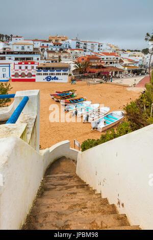 Boats on sandy beach frame the typical fishing village of Carvoeiro Lagoa Municipality Algarve Portugal Europe - Stock Photo