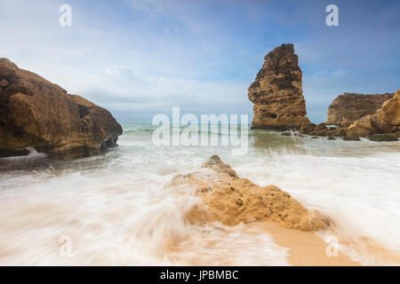 Waves crashing on the sand beach surrounded by cliffs Praia da Marinha Caramujeira Lagoa Municipality Algarve Portugal - Stock Photo