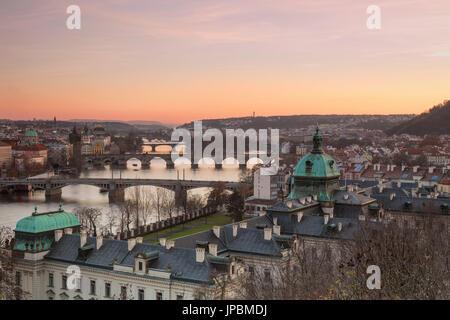 Pink sky on historical bridges and buildings reflected on Vltava (Moldava) river at sunset Prague Czech Republic - Stock Photo