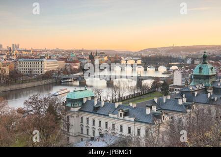 Sunset on the historical bridges and buildings reflected on Vltava (Moldava) river Prague Czech Republic Europe - Stock Photo