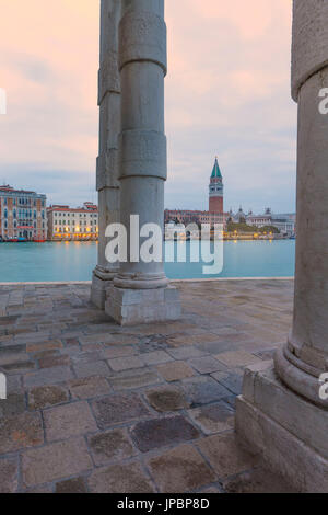 Europe, Italy, Veneto, Venice. View of St. Mark bell tower and buildings on the Canal Grande trough the columns - Stock Photo