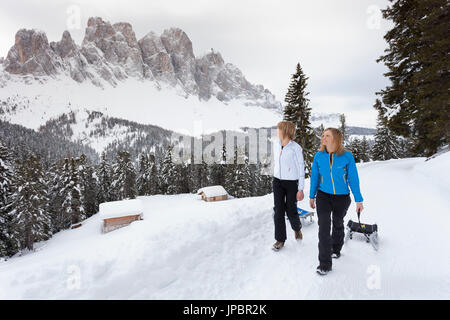 two models are walking with their sleddings along a winter path with the Geisler in the background, Villnoss, South - Stock Photo