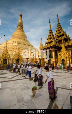 Yangon, Myanmar (Burma). Women sweeping the marble floor of the Shwedagon pagoda. - Stock Photo