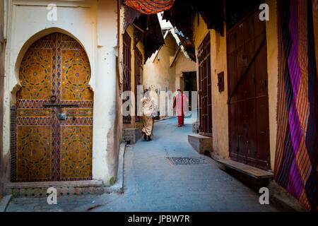 Fes, Morocco, North Africa. Passers in the narrow streets of the medina. - Stock Photo
