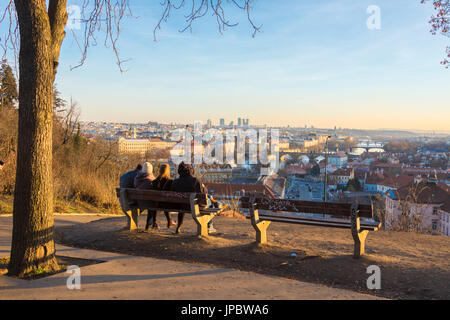 People on a bench admire the historical buildings  and bridges on Vltava (Moldava) river at sunset Prague Czech - Stock Photo