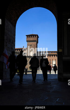 Silhouettes under the arch framing the ancient Sforza Castle Milan Lombardy Italy Europe - Stock Photo