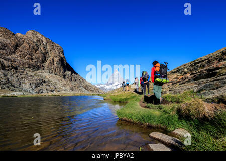 Hikers proceed on the shore of Lake Riffelsee with Matterhorn in the background Zermatt Canton of Valais Switzerland - Stock Photo