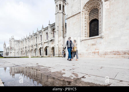 Tourists walk beside to the Jeronimos Monastery which is reflected in a pool Santa Maria de Belem in Lisbon Portugal - Stock Photo