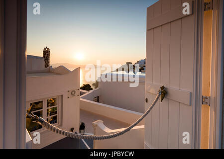 Sunset on Aegean Sea seen from a typical Greek house in the old village of Firostefani Santorini Cyclades Greece - Stock Photo