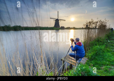 Photographer in action shooting the windmill reflected in the canal Kinderdijk Rotterdam South Holland Netherlands - Stock Photo