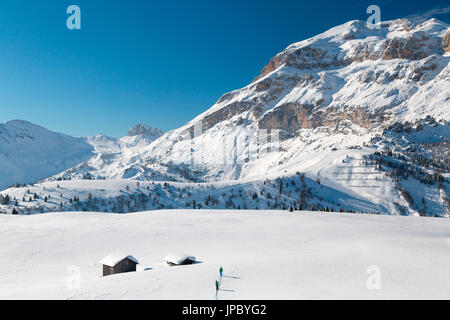 Hikers on snowshoes in the snowy valley framed by wooden huts at Cherz Arabba Dolomites Veneto Italy Europe - Stock Photo