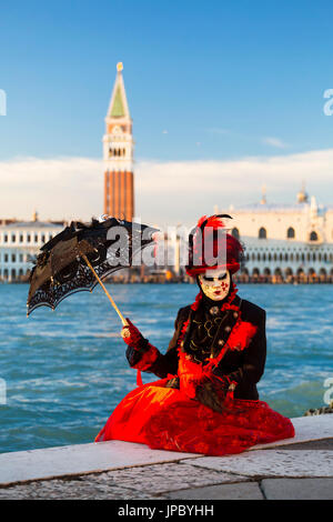 Portrait of woman with red costume and typical mask of Carnival of Venice with St Mark's Square in the background - Stock Photo