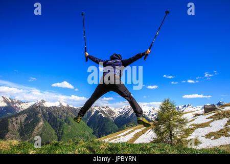 Hiker performs spectacular stunts on the slopes of Rosetta peak. Rasura. Valgerola. Valtellina. Lombardy. Italy. - Stock Photo