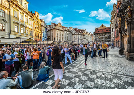 A large crowd of tourists gather at the Astronomical Clock in Old Town Prague and a sunny day - Stock Photo