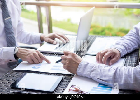 Business people discuss together about there work by graph document and setting in outdoor for planning financial - Stock Photo