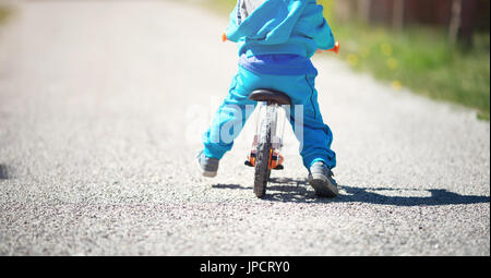 children riding on a bicycles at gravel road in the park in summer - Stock Photo