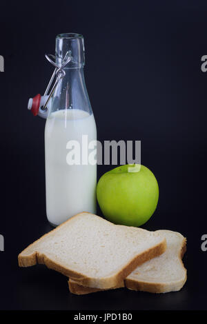 Energy breakfast for diet Bread, milk and green apple on black background - Stock Photo