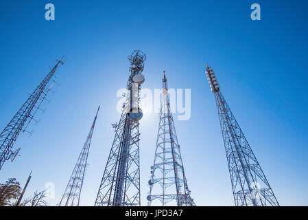 looking up at multiple television, radio and mobile phone towers on Mt Conobolas near Orange in Western NSW, Australia - Stock Photo