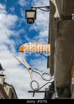 Scissors sign for hairdresser, Laruns, France. - Stock Photo
