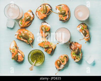 Crostini with smoked salmon and pink grapefruit cocktails, flat-lay - Stock Photo