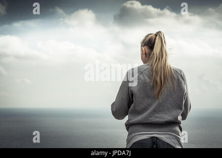 Young blonde smiling woman portrait with with blurred mountains landscape on background in overcast day - Stock Photo