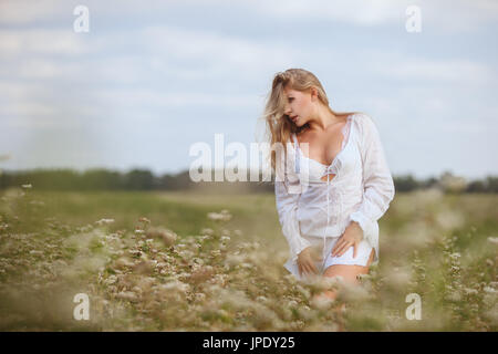 Beautiful woman in a field among the tall grass is nurtured by nature. - Stock Photo