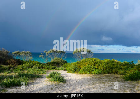 Rainbow and stormy skies over Seven Mile Beach, Forster, New South Wales, NSW, Australia - Stock Photo