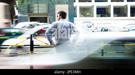 Belgrade, Serbia - June 21, 2017: Young bearded man in blue shirt waiting for the bus in city traffic rush hour - Stock Photo