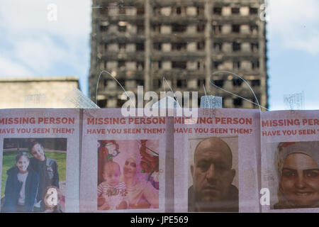 A bus stop displays posters of missing people following the devastating fire, the charred remains of Grenfell Tower - Stock Photo