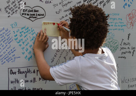 A young boy draws a message on the memorial wall for those who lost their lives in the Grenfell Tower fire. - Stock Photo