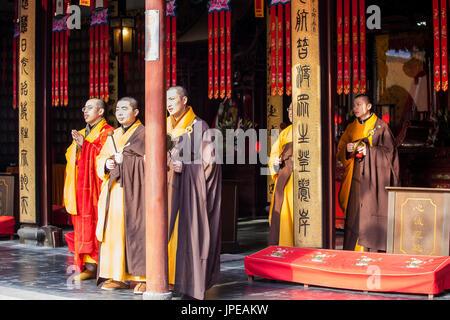 China, Shanghai, Monks inside the Jade Buddha Temple - Stock Photo