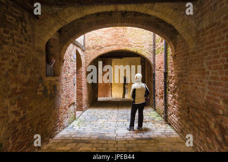 A tourist observes the architecture of a street in the historic center of Buonconvento.  Buonconvento, Ombrone valley,Crete - Stock Photo