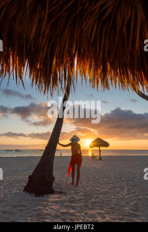 Bavaro Beach, Bavaro, Higuey, Punta Cana, Dominican Republic. Woman by thatch umbrellas on the beach at sunrise - Stock Photo
