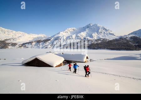Hikers on snowshoes enjoy walking in the snow near the huts of Spluga above Maloja Pass. Canton of Graubunden. Engadine. - Stock Photo