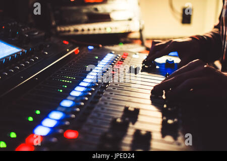 The hands of the sound engineer on the mixing console - Stock Photo