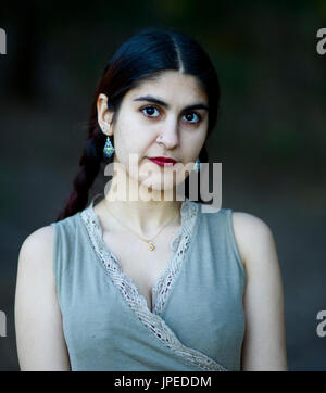 Young Persian Woman poses for photos in a Park - Stock Photo