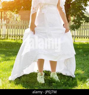 Funny beautiful bride wearing green running shoes. Runaway Bride, close up - Stock Photo