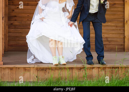 Funny beautiful wedding couple. Bride wearing green running shoes. Runaway Bride, close up - Stock Photo