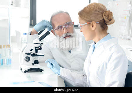 Team of mature scientists working together in lab and looking at each other - Stock Photo