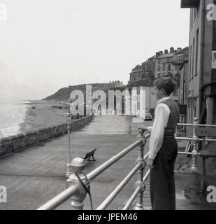 Late 1940s, young boy stands by railings looking over the sea and beach at Cromer, Norfolk, England. - Stock Photo
