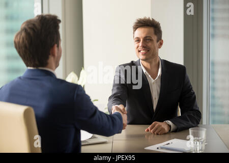 Two cheerful businessmen shaking hands, starting job interview o - Stock Photo