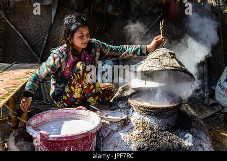 INLE LAKE, MYANMAR - FEBRUARY 15, 2014: young burmese lady cooking rice bred - Stock Photo