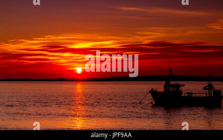 Glorious Sunset over the River Stour at Mudeford Quay , Dorset , with boats  in silhouette on a beautiful Autumn - Stock Photo