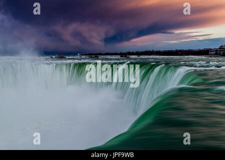 Thundering water pours over the Horseshoe falls At Niagara Falls, Ontario ,Canada ,whilst a threatening sky build - Stock Photo