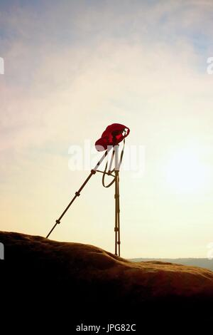Tripod with red baseball cap on the peak ready for photography. Sharp autumn rocky peaks increased from gold fog. - Stock Photo
