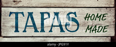 closeup of a rustic wooden signboard with the text tapas homemade written in it - Stock Photo