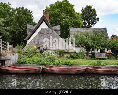 Row boats moored in front of Bridge Cottage at Flatford, Suffolk, England, United Kingdom. - Stock Photo