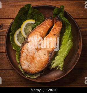 Baked trout steak in pottery with salad and slices of lemon, top view - Stock Photo